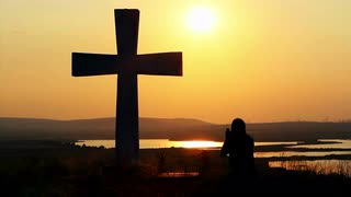 silhouette-of-man-praying-under-the-cross-at-sunset-sunsrise_4kpkhgsr__S0000